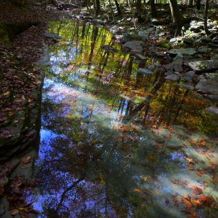 Creek reflection across gray stone and red leaves on OHT