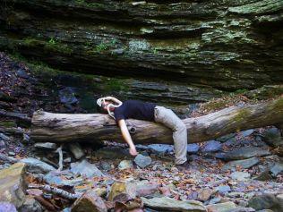 john ozmore and face hugger on log under bluff