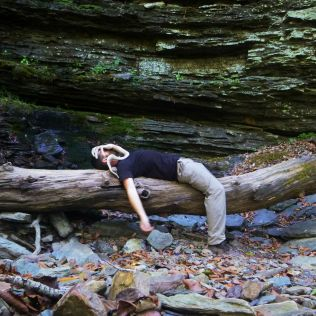 john ozmore and face hugger on log under bluff